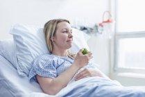 Paziente sdraiato nel letto d'ospedale a mangiare mela — Foto stock