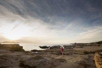 Female toddler on coastal rock at sunset, Calvi, Corsica, France — Stock Photo