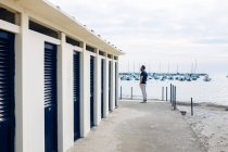 Male tourist next to changing block by the sea, Tuscany, Italy — Stock Photo