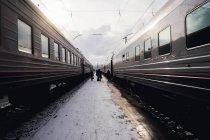 Menschen zu Fuß zwischen zwei Zügen, Ural, Russland — Stockfoto