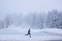Distant view of male runner running in deep snow, Gstaad, Switzerland — Stock Photo