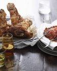 Garretti prosciutto arrosto con contorno e bevande bicchieri sul tavolo — Foto stock
