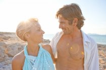 Пара отдыхает на пляже, смотрит друг на друга, солнце на заднем плане — стоковое фото