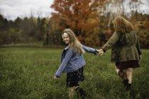 Mutter und Tochter, die Hand in Hand gehen auf Wiese, Lakefield, Ontario, Kanada — Stockfoto