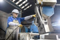 Worker cleaning sand mould in foundry — Stock Photo