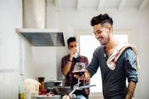 Pareja masculina preparando comida en la cocina, bebiendo vino - foto de stock