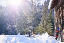 Woman practicing bow yoga pose by log cabin in snow,  Austria — Stock Photo