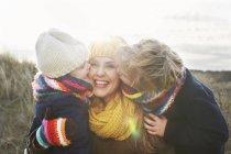Середині дорослу жінку з сином і дочкою цілуватися щокою на узбережжі — стокове фото