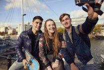 Três amigos sentados ao ar livre, tendo selfie com câmera, Bristol, Reino Unido — Fotografia de Stock