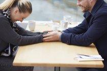 Jeune couple assis à table de café, main dans la main, rire — Photo de stock