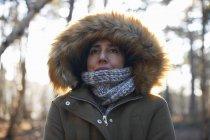 Retrato de mulher madura usando capuz de pele e cachecol na floresta — Fotografia de Stock