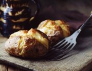 Home-made jacket potatoes with cheddar cheese on rustic wooden board — Stock Photo