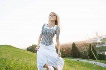 Jeune femme en cours d'exécution sur la colline du parc — Photo de stock