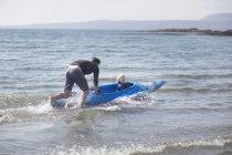 Père fils poussant dans l'eau en canoë — Photo de stock