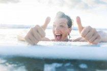 Frau mit Surfbrett im Meer geben Daumen nach oben, Nosara, Provinz Guanacaste, Costa Rica — Stockfoto