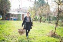 Vista frontal de longitud completa de mujer joven en canasta de mimbre con jardín - foto de stock
