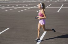 Young female runner running in city parking lot — Stock Photo