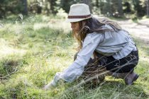 Mature woman foraging for mushrooms in forest — Stock Photo
