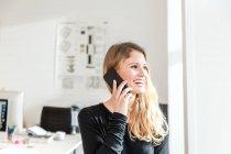 Молода жінка в офісі за допомогою смартфона робить телефонний дзвінок, дивлячись на посмішку. — стокове фото