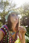 Mature woman wearing sunhat and sunglasses blowing dandelion seeds — Stock Photo
