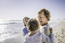 Padre che porta i figli in braccio sulla spiaggia — Foto stock