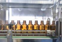 Стеклянные бутылки в ряд на фармацевтической фабрике — стоковое фото