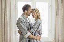 Портрет середині дорослих пара носити халати, обіймати — стокове фото