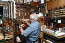Senior man selecting tools in traditional bookbinding workshop — Stock Photo