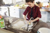 Little boy washing up dishes in kitchen — Stock Photo