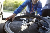 Cyclist removing bicycle from car boot — Stock Photo