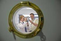 Репетитор преподавания судоходства курсанта, как использовать секстант, просмотр через иллюминатор корабля — стоковое фото