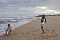 Junger Mann kniet am Strand, junge Frau steht in Herzform — Stockfoto