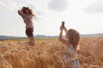 Mädchen nehmen Foto von Mutter im Weizen Feld springen — Stockfoto