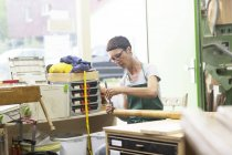 Woman in workshop making alphorn — Stock Photo