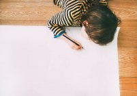 Overhead view of boy drawing on large paper on floor — Stock Photo