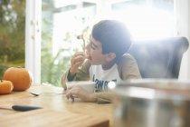 Niño comiendo sopa de calabaza en la cocina - foto de stock