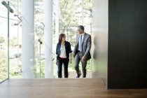 Businessman and woman walking up stairs in modern building — Stock Photo