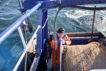 Fischer bringt Fang auf Trawler — Stockfoto