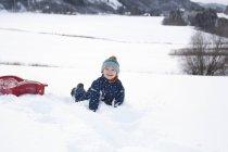 Junge auf seinem Schlitten im Schnee spielen — Stockfoto