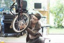 Woman in bicycle workshop repairing wheel on recumbent bicycle — Stock Photo