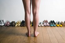 Legs in front of row of shoes — Stock Photo