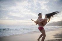 Середине Взрослый пара на пляже, мужчина женщина переноски оружия, вид сзади — стоковое фото