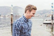 Молодой человек на берегу озера, озеро Комо, Италия — стоковое фото