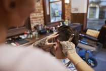 Hairdresser shaving customer's hair with straight razor — Stock Photo