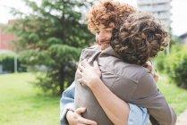 Друзья обнимаются в парке — стоковое фото