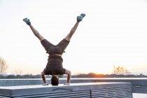 Mitte erwachsenen Mannes balancieren auf Kopf, in Yogaposition Rückansicht — Stockfoto