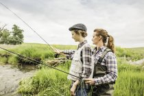 Side view of mother and daughter fishing in river — Stock Photo