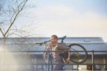 Бізнесмен працює з велосипедом і папки в руках — стокове фото