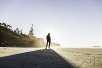 Man looking out from Long Beach at sunrise, Pacific Rim National Park, Vancouver Island, British Columbia, Canada — Stock Photo