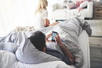 Мужчина в постели с помощью смартфона, женщина, сидящая в конце кровати — стоковое фото